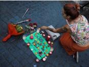 Женщина кладет свечу на плакат, читает на испанском и каталонском языках «Каталония, место мира», в районе, где фургон врезался в пешеходов на улице Лас-Рамблас в Барселоне, Испания 18 августа 2017 года.
