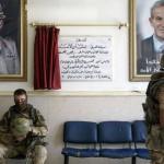Вежливые люди в здание возле портретов Асада и его отца