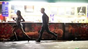 Женщина и мужчина бегут с концерта, где уже вовсю идет пальба из гостиницы
